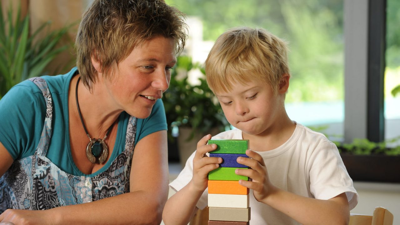 Boy and teacher making a tower of colored blocks. Photo credit: EVAfotografie; Getty Images