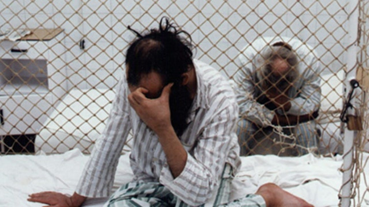 Two people inside netted cage beds